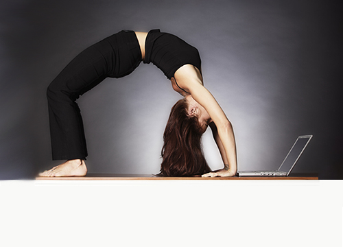 Woman in yoga pose looking at laptop