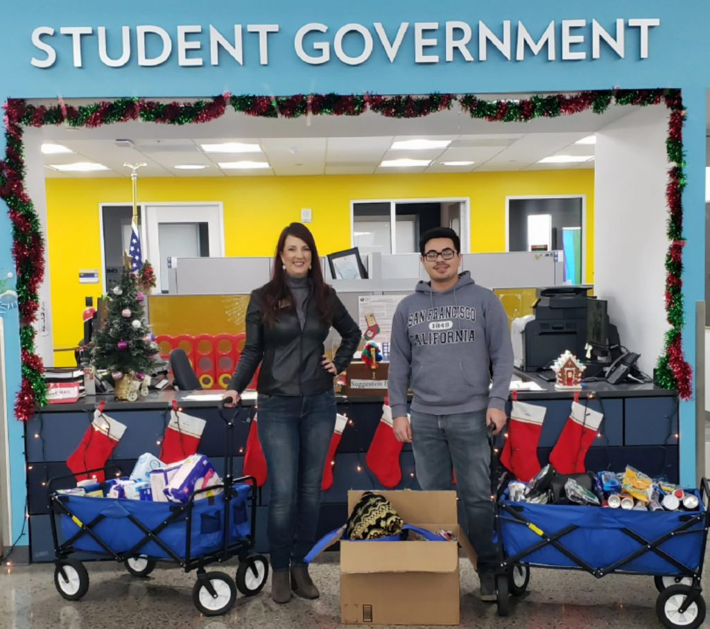 epartment of Communication Professor Charlene S. Gibson and one of her students, Brian Arreola, stand with their #TeamGibsonGives Coyote Cupboard donation, part of a group advocacy project in their COM 115 Applied Communication classes.